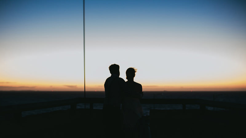 couple silhouetted against sunset during engagement shoot