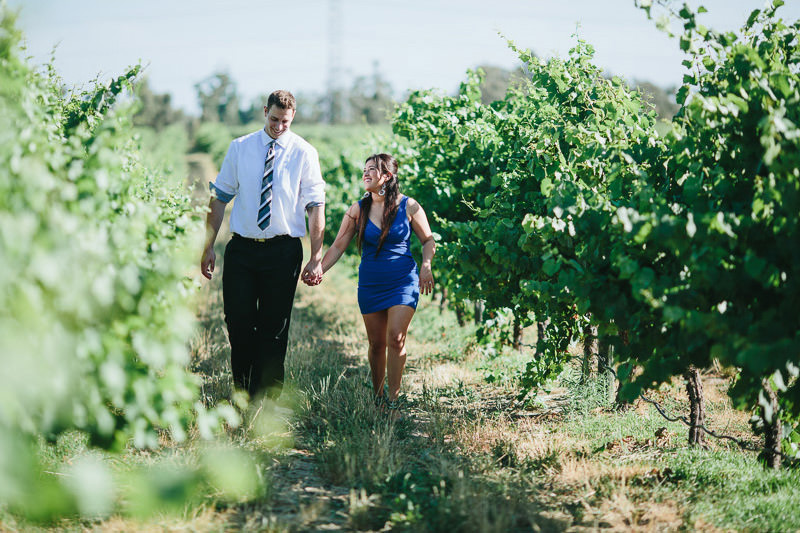 couple walking through vines in swan valley perth