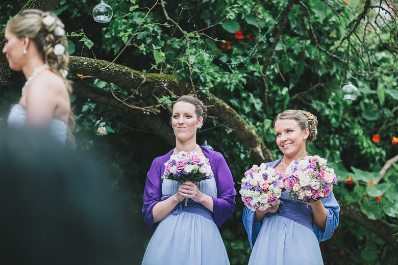 Bridesmaids watching wedding ceremony, unique flowers, purple dress
