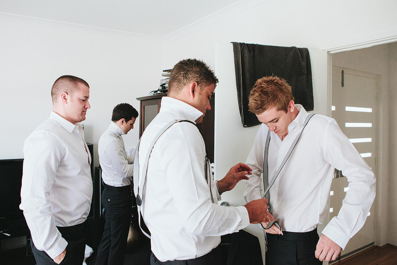 groom fixing groomsman's suspenders