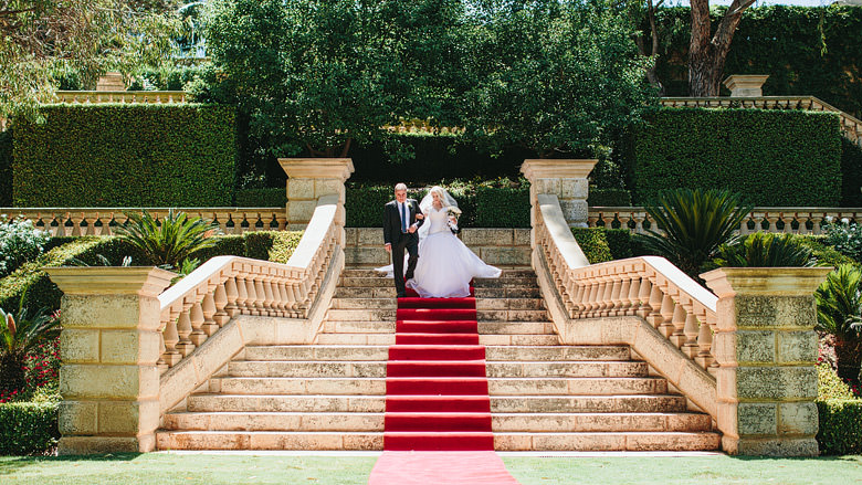 bride and her father descending stairs to aisle