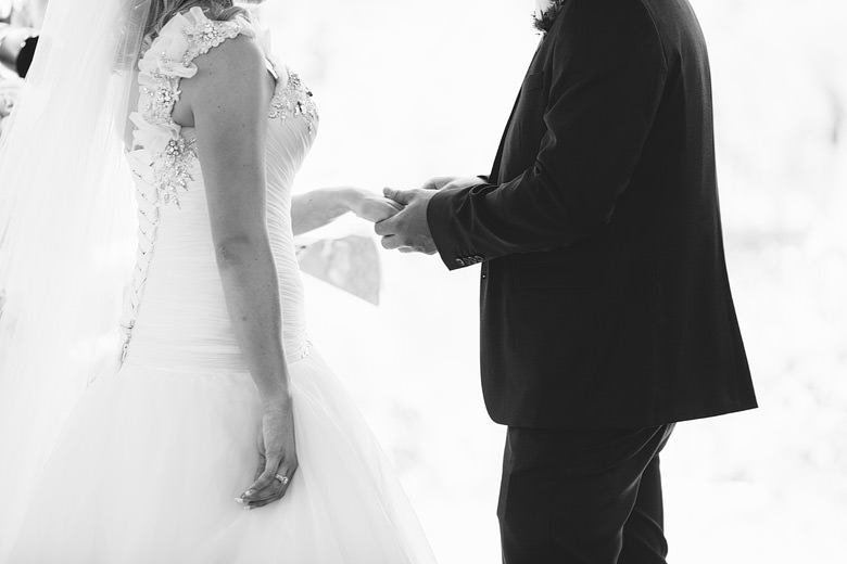 groom holding bride's hand and exchanging ring