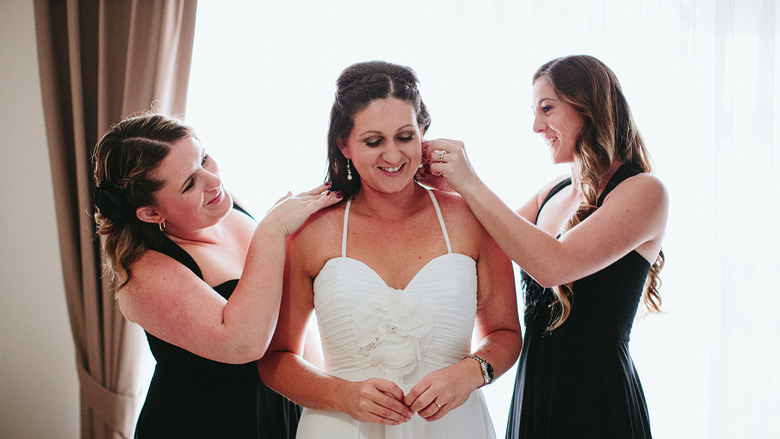 bridesmaids dressing bride and putting on her earrings