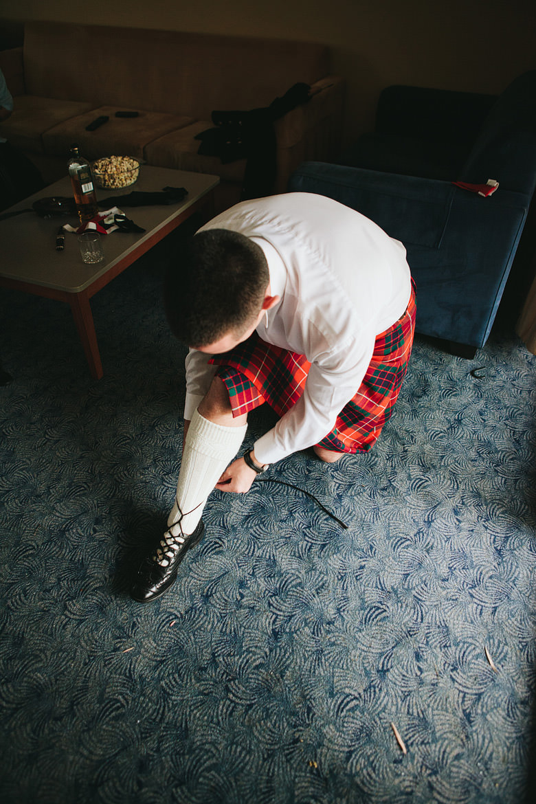 scottish groom putting on his kilt and shoes