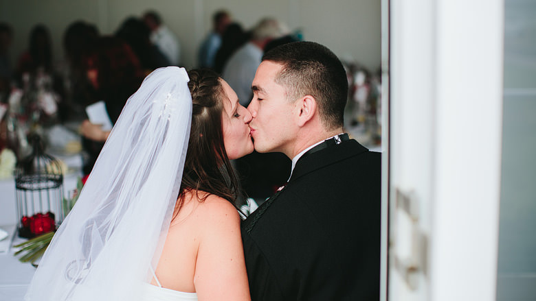 bride and groom sharing a sneaky kiss