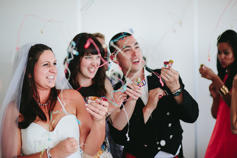 couple popping party poppers during wedding