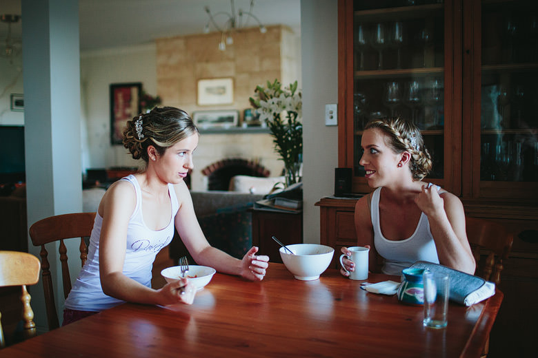 bride and bridesmaid eating breakfast candid