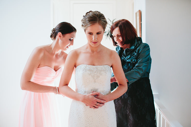 bridesmaid and mother of bride doing up wedding dress