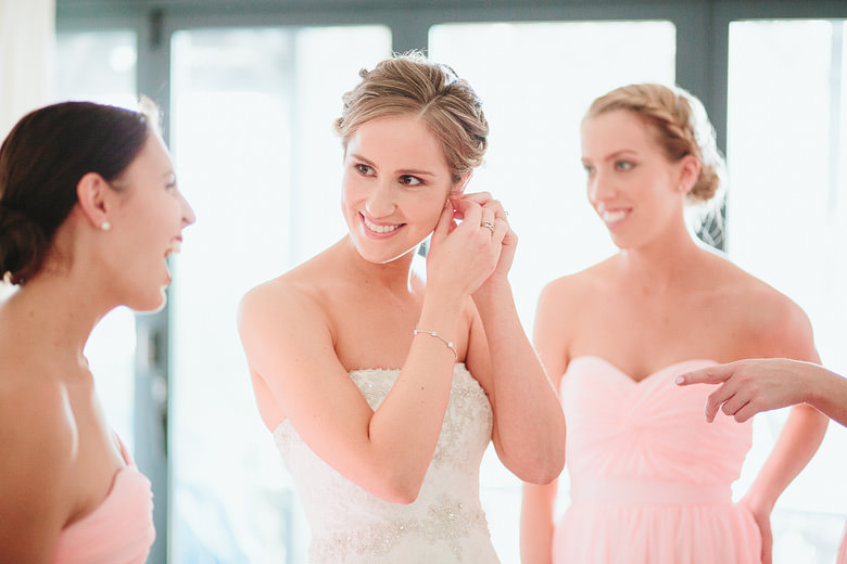 bridesmaids watching bride put on her earings
