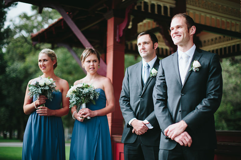 smiling groom watching bride walk down aisle