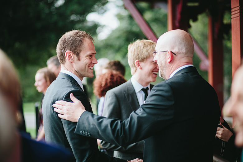 father congratulating groom after ceremony