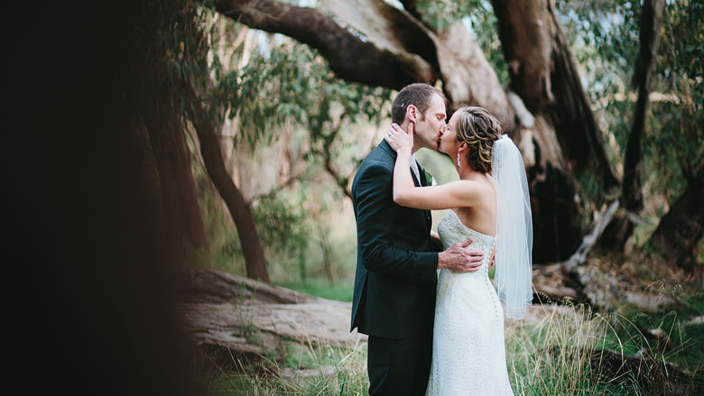 bride and groom kiss amongst trees in Kings Park
