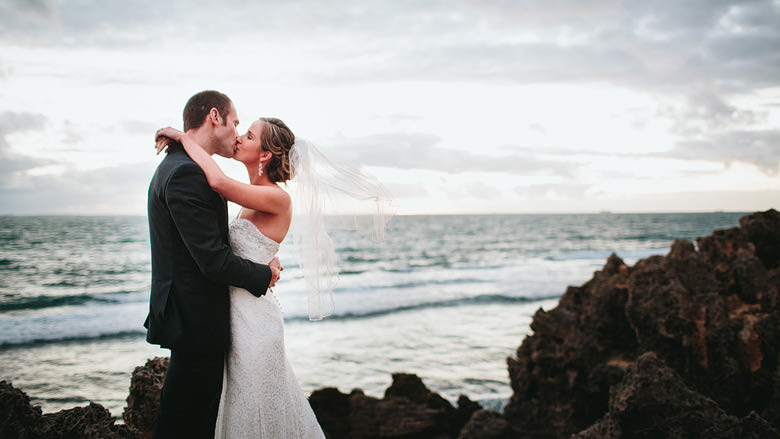 bride and groom kissing on beach cliffs location