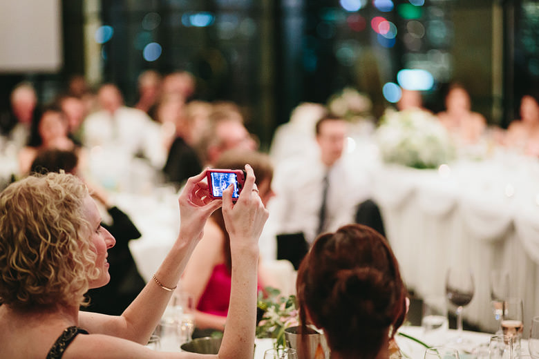 guest taking photograph of bride and groom