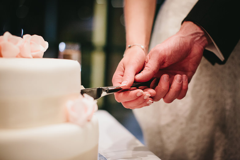 detail of bride and groom's hands cutting wedding cake