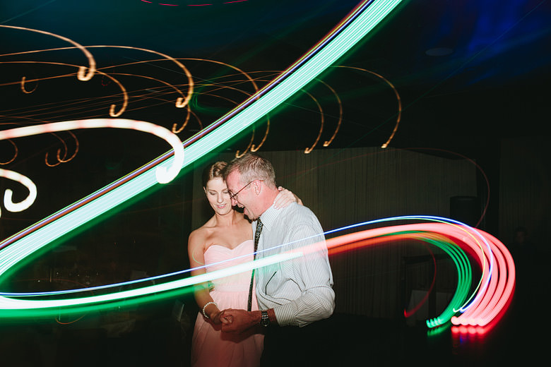 bridesmaid dancing with father light painting at wedding reception
