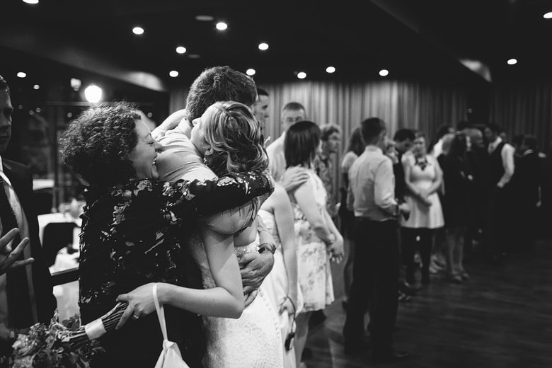 bride being hugged and congratulated by loved ones